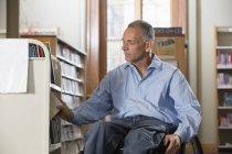 Homem em uma cadeira de rodas com uma lesão medular organizando livros em uma biblioteca — Fotografia de Stock