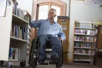Man in a wheelchair with a Spinal Cord Injury moving a shelf of books in a library — Stock Photo