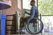 Человек, у которого был менингит позвоночника в инвалидной коляске с помощью лифта вместо лестницы — стоковое фото
