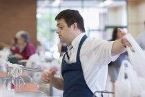 Человек с синдромом Дауна работает в продуктовом магазине — стоковое фото