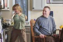 Жінка з синдромом Тар забирає ніж зі своїм чоловіком на кухні. — стокове фото