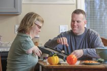 Woman with TAR Syndrome and her husband grating vegetables in the kitchen — Stock Photo