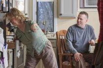 Frau mit Teersyndrom benutzt mit ihrem Mann eine Küchenschublade — Stockfoto