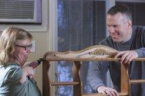 Жінка з синдромом Тар за допомогою електричної пилки зі своїм чоловіком. — стокове фото