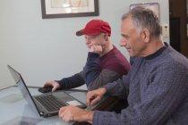 Père avec lésion médullaire et fils avec syndrome de Down avec ordinateur portable à la maison — Photo de stock