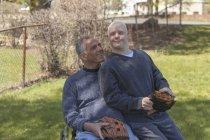 Отец с травмой спинного мозга и сын с синдромом Дауна собираются играть в бейсбол в парке — стоковое фото