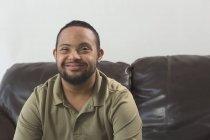 Щасливий афроамериканець людина з синдромом Дауна сидячи на дивані будинку — стокове фото