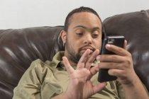 Felice uomo afroamericano con sindrome di Down utilizzando smartphone a casa — Foto stock