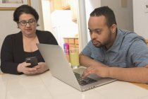 Happy African American man with Down Syndrome using laptop  with mother at home — Stock Photo