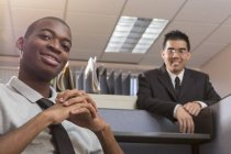 Hombre afroamericano y asiático con autismo trabajando en la oficina - foto de stock