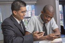 Афроамериканец и азиат работают в офисе — стоковое фото