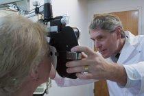 Офтальмолог осматривает глаза женщины с помощью фотоптера — стоковое фото