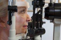 Femme obtenant examen de la vue avec une lampe à fente dans la clinique — Photo de stock