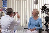 Médecin retirant l'air de la seringue en clinique — Photo de stock