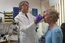 Офтальмолог делает инъекцию ботокса пациенту — стоковое фото