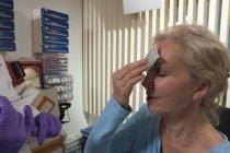 Patientin trägt nach Botox-Behandlung Eis auf der Stirn auf — Stockfoto