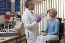 Ophtalmologiste injectant du Botox à un patient — Photo de stock