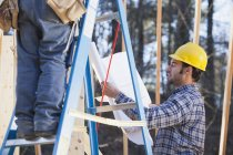 Плотник объясняет планы строительства домов — стоковое фото