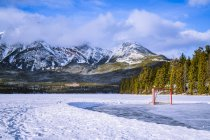 Frozen Pyramid Lake with hockey net on a cleared ice rink in winter, Jasper National Park; Alberta, Canada — Stock Photo
