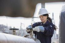 Жіночий енергетик регулює водяні клапани на електростанції. — стокове фото