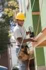 Carpinteiro usando arma de prego em afiação de nova casa — Fotografia de Stock
