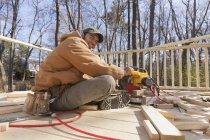 Hispanic carpenter using chop saw to cut deck railing cap — Stock Photo