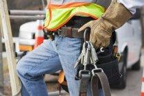 Trabalhador da linha de alimentação com cinto de ferramentas e arnês de segurança em seu caminhão — Fotografia de Stock