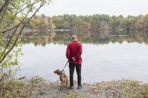 Человек с тревожным расстройством и его собака-терапевт на озере — стоковое фото