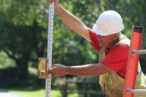Строительный надзиратель с помощью электронного зондирующего стержня — стоковое фото