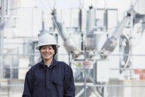 Portrait d'une ingénieure en puissance devant un transformateur haute tension à une centrale électrique — Photo de stock