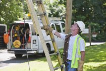 Communications worker preparing to climb ladder for overhead wiring — Stock Photo