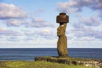 Un unico moai su uno sfondo blu di cielo, nuvole e oceano; Isola di Pasqua, Cile — Foto stock