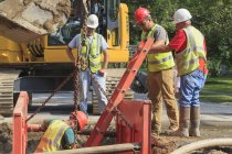 Travailleurs de la construction se préparant à descendre le trou avec échelle — Photo de stock