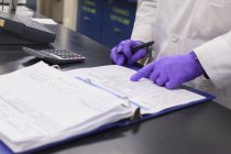 Lab technician recording data from sample test — Stock Photo