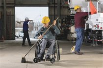 Maintenance technicians, one with a spinal cord injury, cleaning in utility truck garage at electric power plant — Stock Photo