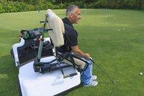Человек с травмой спинного мозга в адаптивной тележке в гольф положить зеленый — стоковое фото