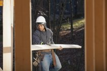 Carpenter carrying a board for house construction — Stock Photo