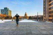 Homem usando uma máscara e luvas segurando as mãos na cabeça enquanto caminhava em um caminho pelo Legislativo durante a pandemia mundial de Covid-19; Edmonton, Alberta, Canadá — Fotografia de Stock