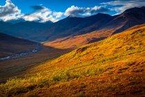 Brooks Mountains und Kuyuktuvuk Creek Valley in herbstlichen Farben unter blauem Himmel. Gates of the Arctic National Park and Preserve, Arctic Alaska im Herbst; Alaska, Vereinigte Staaten von Amerika — Stockfoto