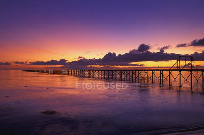 Пир в океане на закате — стоковое фото