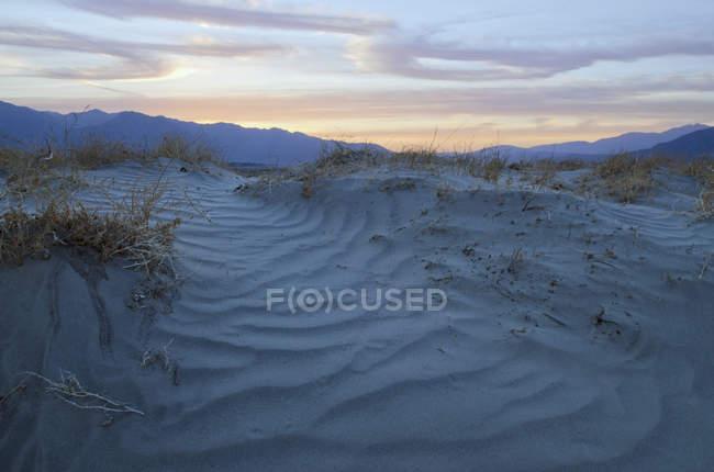 Закат над песчаными дюнами — стоковое фото