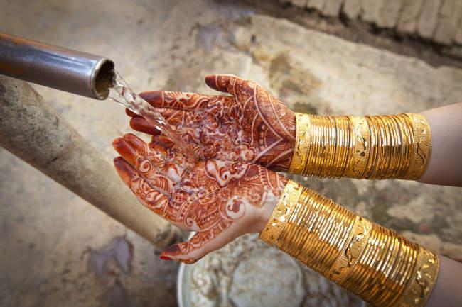 Agua saliendo de la boquilla en las manos cubiertas con Mehndi - foto de stock