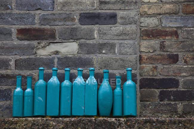 Botellas azules alineadas - foto de stock