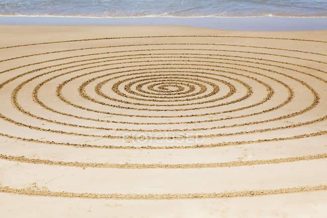 Cercles sur le sable contre l'eau — Photo de stock
