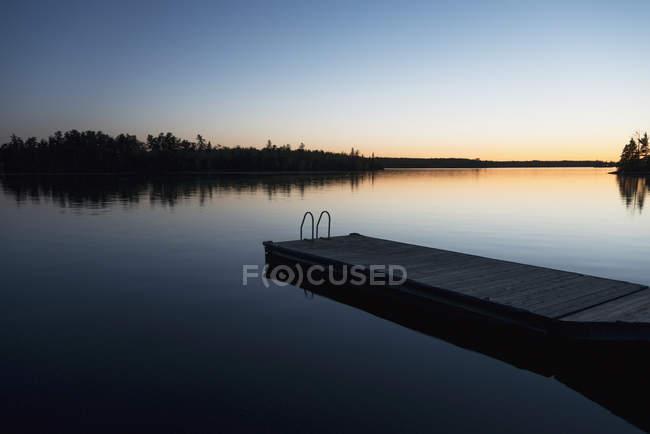 Захід сонця над озеро з дерев'яними док — стокове фото