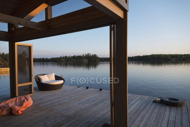 Wooden dock with cushioned seat — Stock Photo