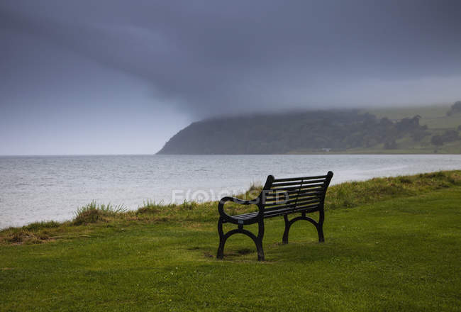 Bench on water edge with storm clouds — Stock Photo