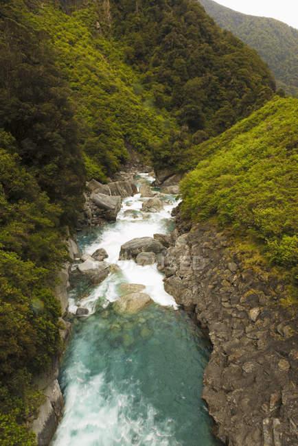Agua del río que atraviesa colinas - foto de stock