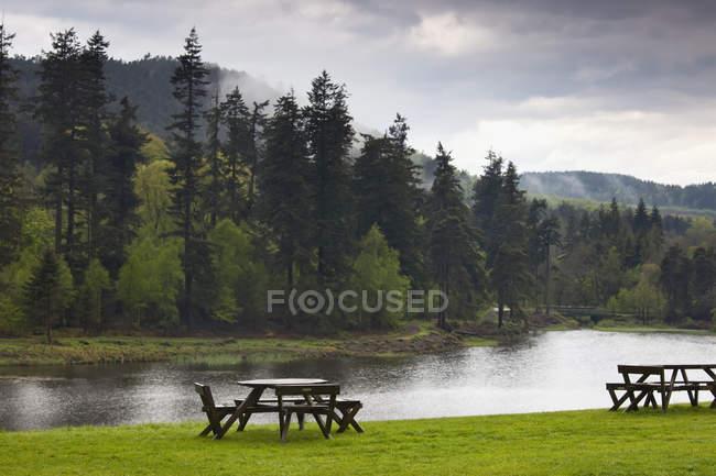 Mesas de piquenique ao longo da borda da água — Fotografia de Stock