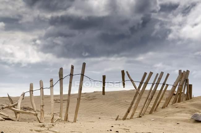 Сломанный забор в песок — стоковое фото